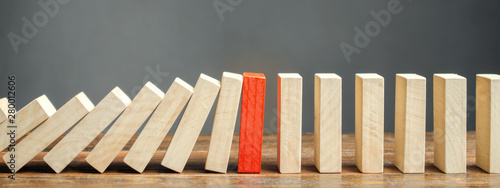 Obraz Wooden blocks and the effect of dominoes. Risk management concept. Successful strong business and problem solving. Reliable leader. Stop the destructive processes. Strategy development. - fototapety do salonu