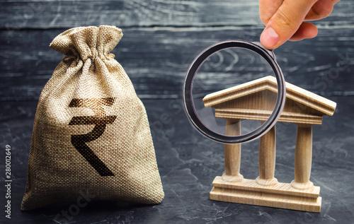A bag with indian rupee (rupiah) and a government building Billede på lærred