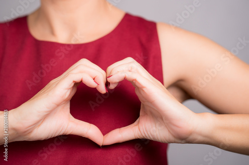 Closeup hands of a beautiful woman in stylish red outfit making heart shape gesture on her chest Canvas Print