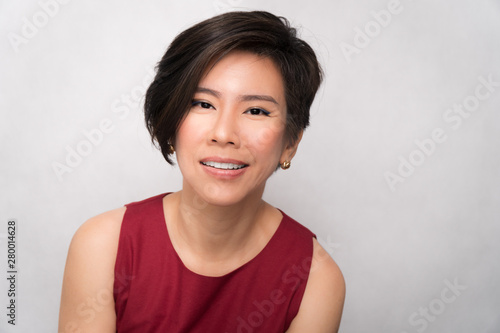 Studio portrait of a beautiful middle aged asian woman (40-50) in stylish red outfit smiling charming and cheerful on white background Poster Mural XXL