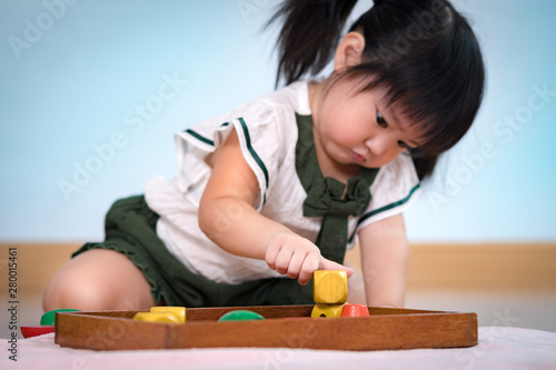 Fotografiet Closeup: A preschool little girl 2-3 years in Montessori classroom deep concentration engaged stacking sensory wooden blocks