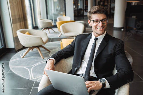 Portrait of satisfied young businessman sitting on armchair with laptop computer in hotel hall