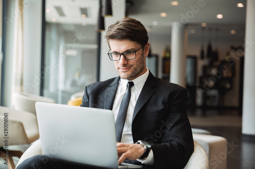Portrait of pleased young businessman sitting on armchair with laptop computer in hotel hall
