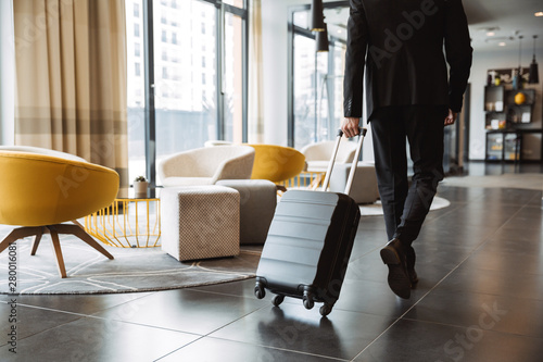 Cropped photo of caucasian businessman wearing suit walking with suitcase in hotel lobby