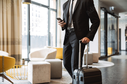 Fototapeta Cropped photo of confident businessman wearing suit holding smartphone and walking with suitcase in hotel lobby obraz
