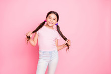 Portrait Of Pretty Kid Touching Pigtails Standing Looking Wearing Trousers White T-shirt Isolated Over Pink Background