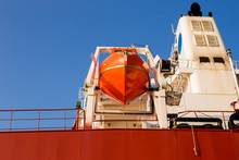 Orange Lifeboat At Tail Of International Cargo Ship In The Ocean For Emergency Evacuation Loading For Safety, Freight Transportation, Shipping, Nautical Vessel.