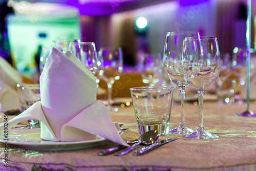 Fényképezés crystal and glass glasses on the served tables for a banquet with color lighting