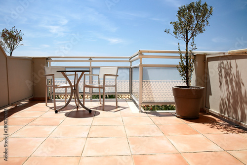 Fotografie, Obraz  A terrace with table and chairs in a blue sky and ocean view.