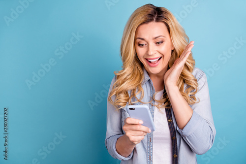 Portrait of astonished lady screaming wow omg holding device isolated reading no Wallpaper Mural