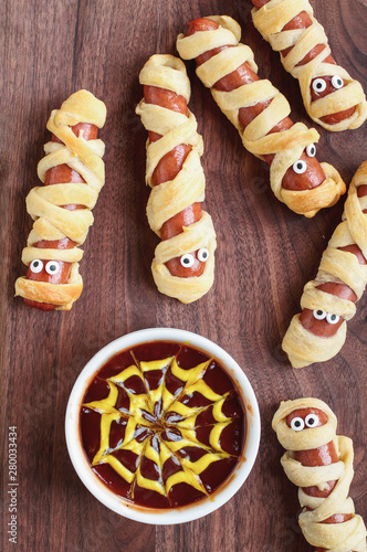 Fun food for kids. Mummy hot dogs lying on a rustic table with a bowl of ketchup and mustard dip, with spider web design. Top view, flay lay position.
