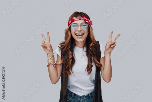 Attractive stylish young woman looking at camera and smiling while standing agai Tableau sur Toile
