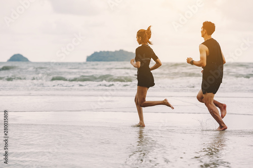 Poster Jogging Runners. Young people running on beach. Athletic attractive people jogging on beach enjoying the sun exercising their healthy lifestyle.