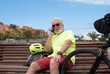 Senior man sitting on a wooden bench resting after an excursion with the e bike. Talking to the phone. Retired people casual clothing. Sea on background. Healthy lifestyle
