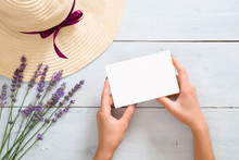 Hands Of Woman Holding Blank Paper Card Mockup Over Rustic Blue Wooden Background With Straw Hat And Lavender Flowers. Flat Lay, Top View, Overhead. Summer Fashion Concept.