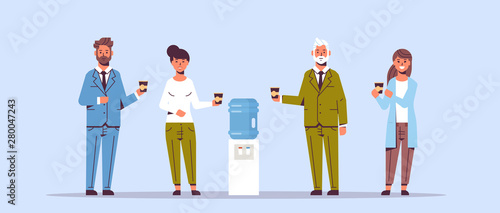 businesspeople office workers talking and drinking water while standing near cooler employees having break concept flat full length horizontal