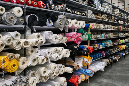 Poster Tissu Fabric warehouse with many multicolored textile rolls