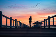 silhouette of healthy woman jogging alone at daily morning on the wooden jetty bridge or pier, daily exercise workout running at light of sunset