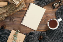Flatlay Hygge Style Composition With Fashion Women Knitted Scarf, Blank Paper Notebook, Mug Of Tea, Gift Box, Firewood On Wooden Background. Flat Lay, Top View, Overhead. Cozy Autumn Home Desk