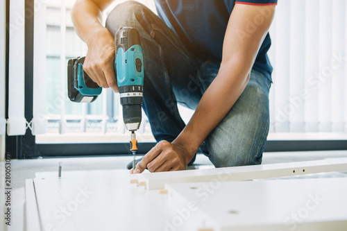 Service man assembling furniture for customer, Delivery service furniture store and assembling for buyer Wallpaper Mural