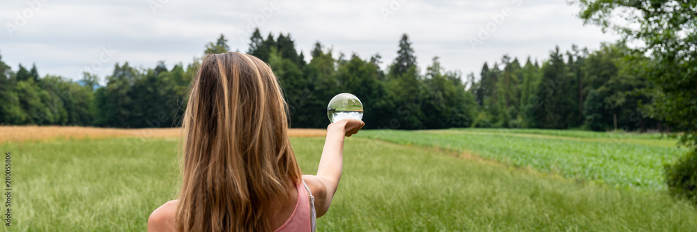 Fototapeta Woman standing in nature holding crystal ball