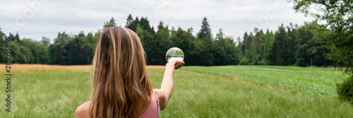 Woman standing in nature holding crystal ball Fototapet