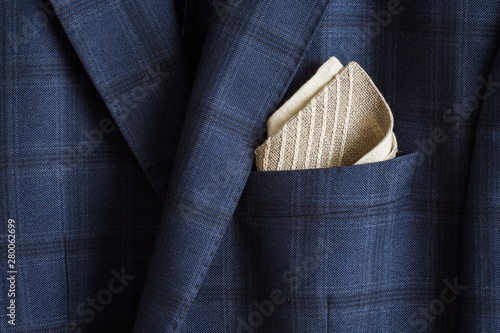 Fototapeta Pocket square with embroidery in the breast pocket of a man's blue suit. Wedding accessories obraz