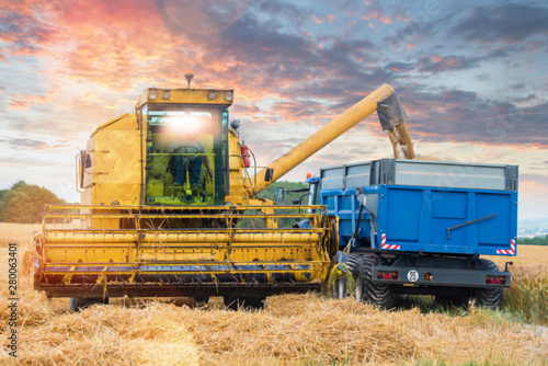 combine and a tractor during the harvest Tablou Canvas
