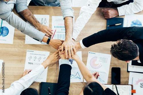 Photo  Crop coworking business people stacking hands above wooden desk with paper docum