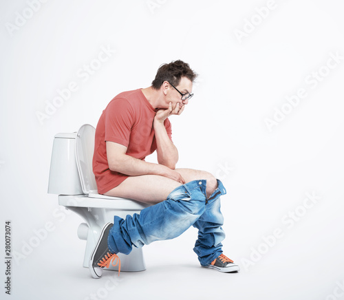 Fényképezés Man in casual clothes and glasses is sitting on the toilet