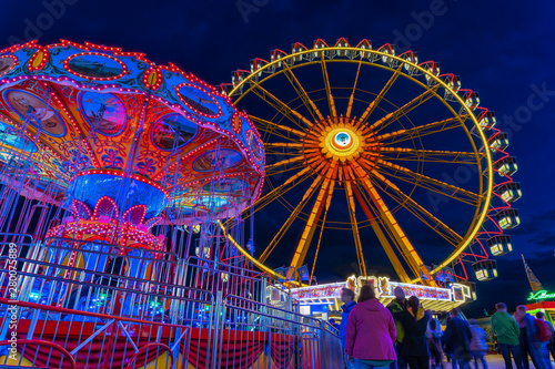 Foto auf Gartenposter Vergnugungspark Spring Festival in Munich at the blue hour with a lightened ferris wheel and chain carusel.