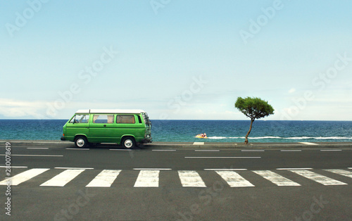 Photo of a green van on the road and sea