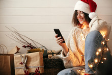 Stylish Happy Girl In Santa Hat Looking At Phone Screen In Festive Christmas Lights On Background O Presents And Gifts In Modern Room. Young Hipster Woman In Cozy Sweater Browsing Online