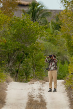 Female Birder With Binoculars, Birdwatching From Dirt Road In The Yucatan Peninsula, Mexico