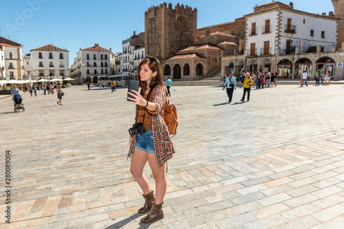 A young red-haired tourist with a backpack makes a selfie in the Plaza Mayor de Caceres