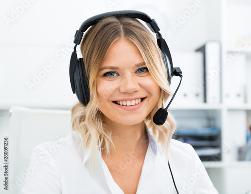 Fotografía  Young call center employee in headphones is sitting near laptop in the office