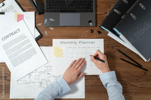 Woman working behind wooden table in office