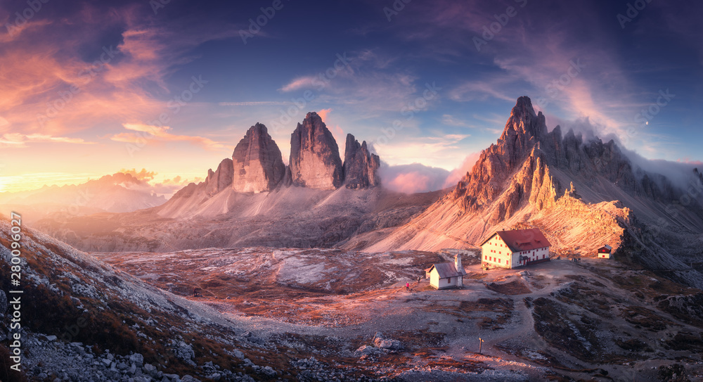 Fototapeta Mountain valley with beautiful house and church at sunset in autumn. Landscape with buildings, high rocks, colorful sky, clouds, sunlight. Mountains in Tre Cime park in Dolomites, Italy. Italian alps
