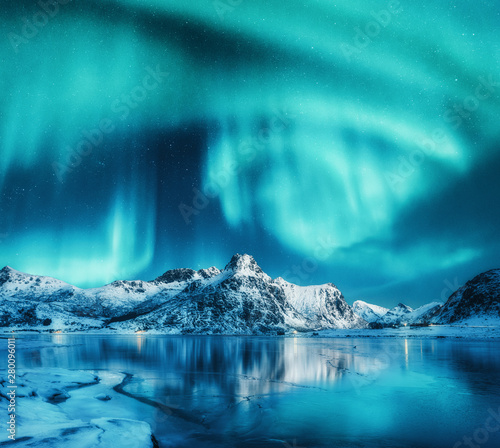 Poster de jardin Aurore polaire Aurora borealis above snowy mountains, frozen sea coast and reflection in water in Lofoten islands, Norway. Northern lights. Winter landscape with polar lights, ice in water. Sky with stars and aurora