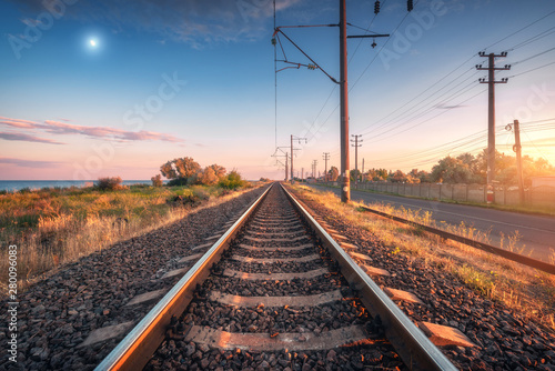 Poster Voies ferrées Railroad and blue sky with moon at sunset. Summer rural industrial landscape with railway station, sky with clouds and gold sunlight, green grass. Railway platform. Transportation. Heavy industry
