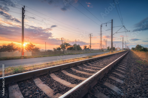 Railroad and beautiful sky at sunset in summer. Rural industrial landscape with railway station, blue sky with colorful clouds and orange sunlight, road. Railway platform. Sleepers. Heavy industry.