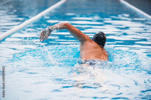 Fotografía  Athletic Young man swimming the back crawl in a pool