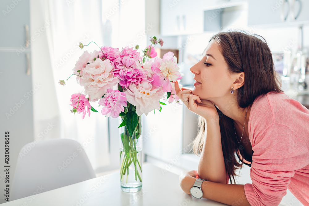Fototapety, obrazy: Woman smelling bouquet of peonies. Housewife enjoying decor and interior of kitchen. Sweet home