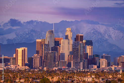 Photo  Downtown Los Angeles skyline with snow capped mountains behind at sunset
