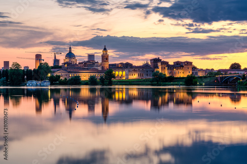 Obraz View of the city of Mantua at sunset reflected on the Middle Lake on the Mincio River - fototapety do salonu