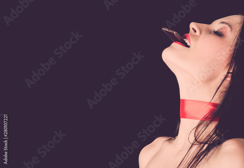 Photo Beautiful woman eating dark chocolate with close eyes