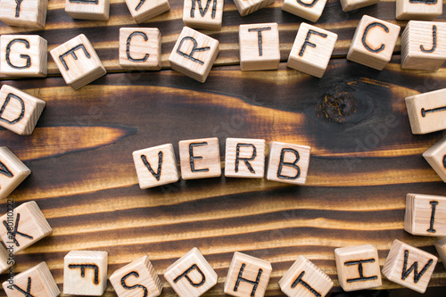Fotografering word verb composed of wooden cubes with letters, Part of speech concept scattere