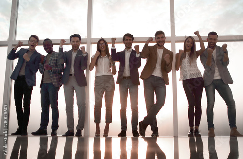 Fotografija  group of young professionals standing in an office with a large window