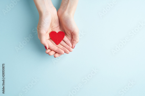 Fototapeta a person holding red heart in hands, donate and family insurance concept, on aquamarine background, copy space top view obraz