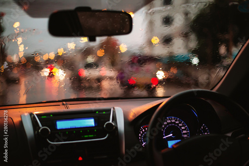 Fototapeta  rain droplets on car windshield, blocked traffic,Inside car with bokeh lights from traffic jam on evening time for background